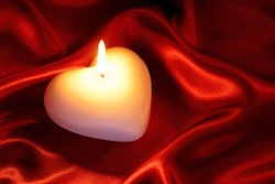 Heart shaped candle on red silk